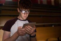 Joven estudiante universitario usando tableta digital en el aula - foto de stock