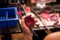 Close-up de mulher segurando escovas e recipiente de tinta vermelha — Fotografia de Stock