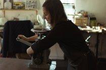 Créatrice de bijoux féminins à l'aide d'une machine en atelier — Photo de stock