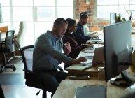 Atentos executivos que trabalham na secretária no escritório — Fotografia de Stock