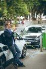 Empresario hablando por teléfono móvil mientras carga coche eléctrico en la estación de carga - foto de stock