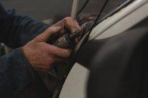 Male mechanic using mini drill machine in garage — Stock Photo