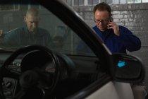 Hombre mecánico de hablar por teléfono móvil en el garaje - foto de stock