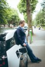 Thoughtful businessman charging electric car at charging station — Stock Photo