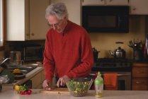 Homem sênior cortando vegetais com faca na tábua de corte na cozinha — Fotografia de Stock