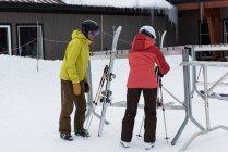 Senior couple arranging ski board on rack in snowy landscape — Stock Photo