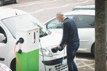 Rückansicht Mann lädt Elektroauto an Ladestation — Stockfoto