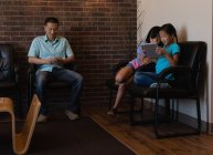 Батько використання мобільного телефону під час дочки, використовуючи цифровий планшетний в стоматологічній клініці — стокове фото