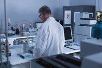 Vue arrière d'un scientifique expérimentant en laboratoire — Photo de stock