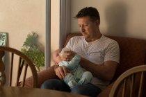 Отец кормит своего малыша молоком в гостиной — стоковое фото