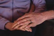 Крупный план пожилой пары, держащейся за руки дома — стоковое фото