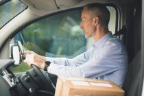 Side view of delivery man with package driving a delivery van — Stock Photo