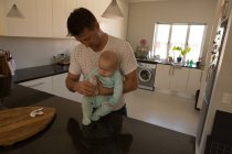 Father and baby boy holding milk bottle in kitchen at home — Stock Photo