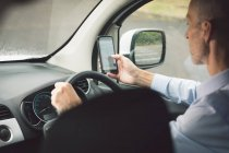 Вид сбоку на доставщика, использующего мобильный телефон за рулем грузового фургона — стоковое фото