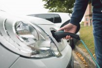 Close-up of man charging electric car at charging station — Stock Photo