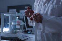 Средняя секция мужского ученого экспериментирует в лаборатории — стоковое фото