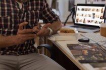 Partie médiane de l'homme d'affaires vérifiant la glycémie avec glucomètre au bureau — Photo de stock