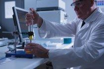 Aufmerksamer männlicher Wissenschaftler experimentiert im Labor — Stockfoto