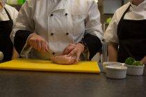 Розділ середині шеф-кухар різання м'яса на Розробні рада кухні — стокове фото