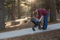 Отец держит своего малыша в парке в солнечный день — стоковое фото