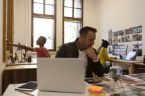 Мужчина-руководитель смотрит на фотографии на столе в офисе — стоковое фото