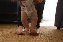 Низкая часть отца помогает своему малышу ходить по дому — стоковое фото