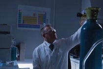 Ученый мужского пола регулирует манометр цилиндра в лаборатории — стоковое фото