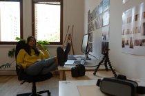 Schöne weibliche Führungskraft hört Musik im Büro mit Beinen auf dem Tisch — Stockfoto