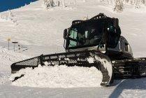 Homme utilisant un camion de chasse-neige pour nettoyer la neige pendant l'hiver — Photo de stock