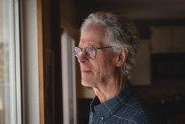 Продуманий старший чоловік дивиться через вікно на дому — стокове фото