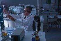 Scientifique masculin attentif expérimentant en laboratoire — Photo de stock