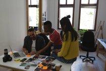 Бізнес колегами, обговорювати над фото на столі в офісі — стокове фото