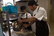 Чоловічі і жіночі шеф-кухар приготування їжі на кухні в ресторані — стокове фото