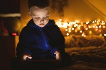 Garçon concentré en veste bleue en utilisant une tablette numérique contre les lumières de Noël — Photo de stock