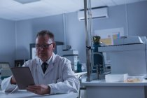 Homme scientifique utilisant une tablette numérique en laboratoire — Photo de stock