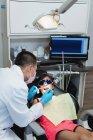Odontólogo masculino examinando a un paciente con herramientas en la clínica — Stock Photo