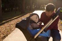 Vater mit seinem kleinen Jungen im Kinderwagen im Park an einem sonnigen Tag — Stockfoto