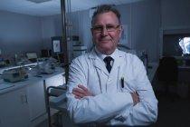 Portrait d'un homme scientifique debout les bras croisés en laboratoire — Photo de stock