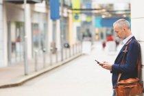 Vista lateral do empresário usando telefone celular na cidade — Fotografia de Stock