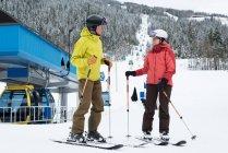 Senior couple in ski attire ready to ski in snowy region — Stock Photo