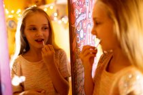 Smiling girl looking in the mirror and applying red lipstick — Stock Photo