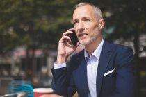 Крупный план бизнесмена, разговаривающего по мобильному телефону в кафе на открытом воздухе — стоковое фото