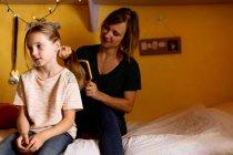 Матері розчісувати волосся дочок на ліжку у себе вдома — стокове фото
