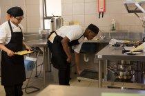 Männlicher Koch öffnet Tür des Backofens in Küche — Stockfoto