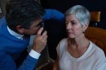 Optometrista che esamina gli occhi del paziente con oftalmoscopio in clinica — Foto stock