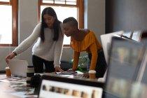 I colleghi di lavoro discutono su un computer portatile sulla scrivania in ufficio — Foto stock