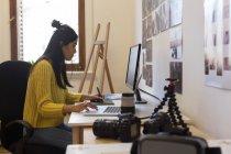 Красивая исполнительница слушает музыку в офисе с ногами на столе — стоковое фото