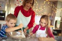 Mère et enfants faire des biscuits de Noël dans la cuisine à la maison — Photo de stock