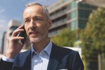 Крупный план бизнесмена, разговаривающего по мобильному телефону в городе — стоковое фото