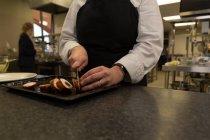Seção intermediária do chef cortando bacon com faca no restaurante — Fotografia de Stock